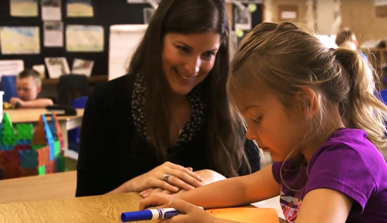 Kindergarten Teacher smiling at her studen while she's drawing